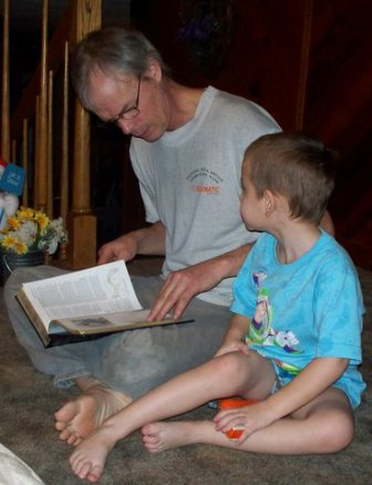 A grandfather reads to his grandson from an encyclopedia.